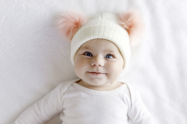 Cute adorable baby child with warm white and pink hat with cute bobbles